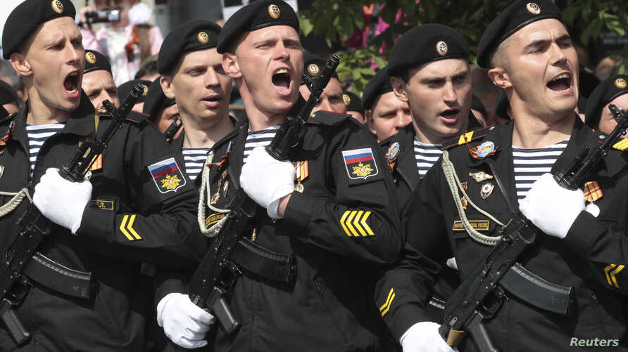 FILE - Russian servicemen march during the Victory Day military parade in Simferopol, Crimea, May 9, 2017.