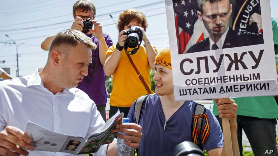 "Russian opposition activist and blogger Alexei Navalny, left, speaks to activists of a National Liberation movement holding a poster with a portrait of him and words reading ""Serve United States of America"" during his visit in Novosibirsk, Russia, Su"