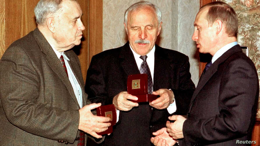 FILE - Russian President Vladimir Putin (R) gives birthday presents to Russian famous actor Mikhail Ulyanov (center) and famous movie director and producer Eldar Ryazanov (left) in his residenence in Novo-Ogaryovo outside Moscow, November 20, 2002.