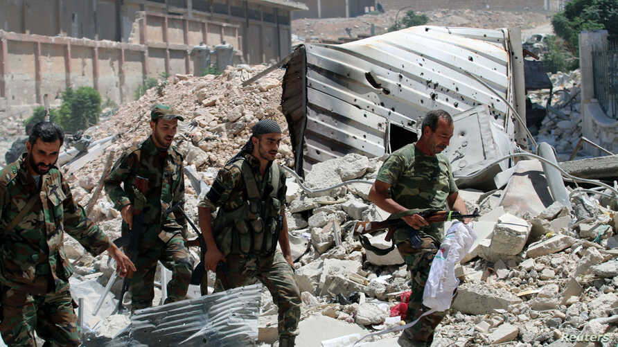 Forces loyal to Syria's President Bashar al-Assad walk with their weapons past rubble after they advanced on the southern side of the Castello road in Aleppo, Syria, in this handout picture provided by SANA on July 28, 2016.