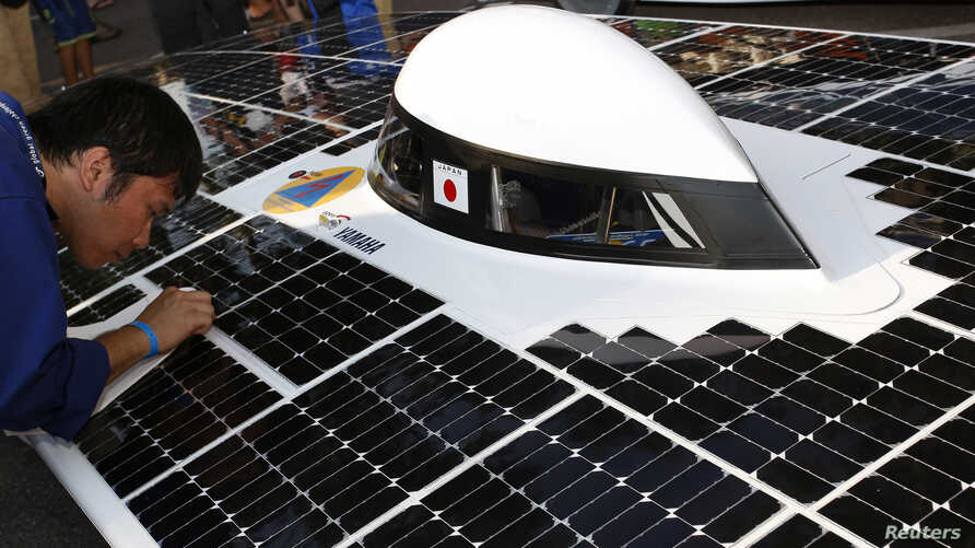 FILE - A members of Japan's team at a previous World Solar Challenge is seen cleaning a solar panel on his vehicle.