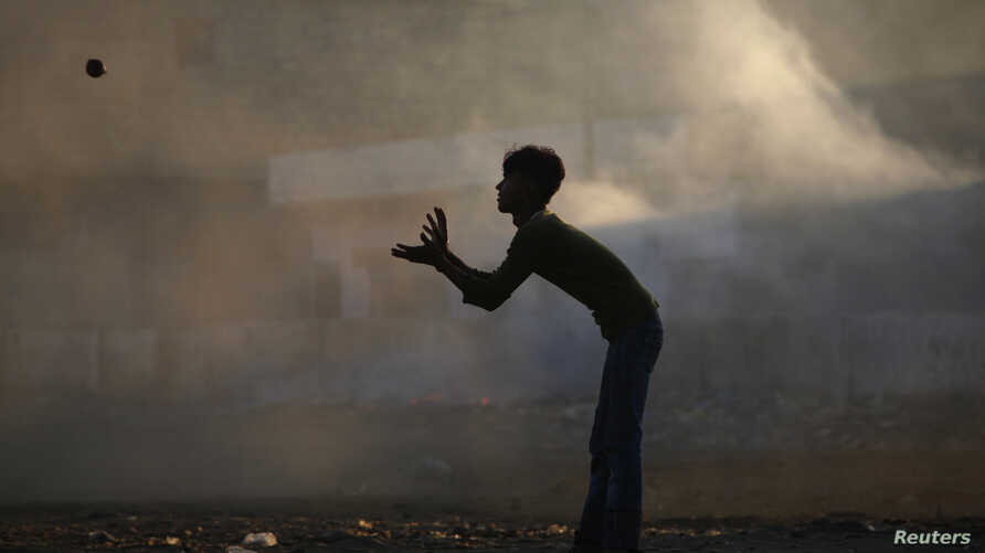 A boy is silhouetted against smoke while playing cricket in a littered ground in a slum area on the outskirts of Karachi, Oct. 18, 2011.