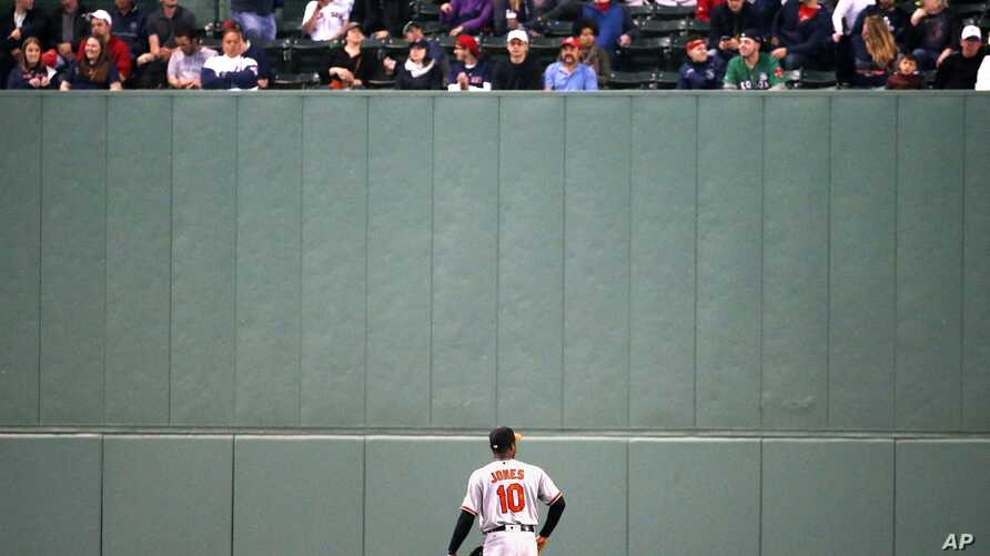 Baltimore Orioles' Adam Jones looks up at fans in center field during the third inning of a baseball game against the Boston Red Sox, May 2, 2017, in Boston.