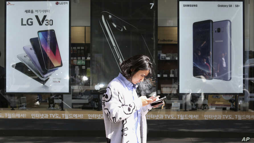 FILE - A woman walks by posters adverting smartphones at a mobile phone store in Seoul, South Korea, Oct. 17, 2017.