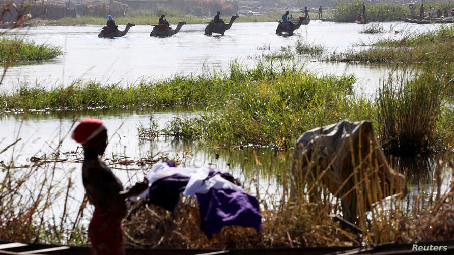 FILE - Men on camels cross the water as a woman washes clothes in Lake Chad in Ngouboua, Jan. 19, 2015