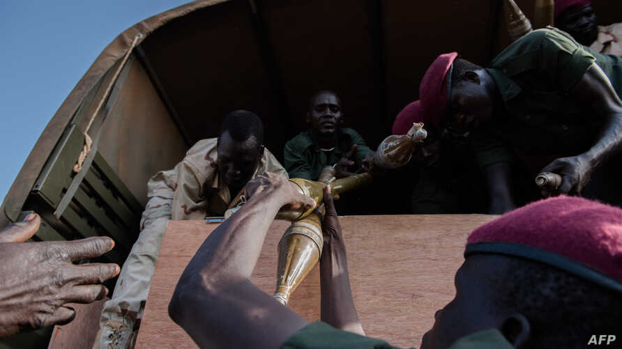FILE - Rebel troops of the Sudan People's Liberation Army in Opposition (SPLA-IO) unload their weapons at their military site in Juba on April 25, 2016.