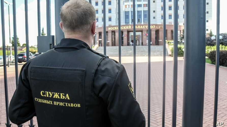 FILE - A guard stands behind a fence at the main entrance of Moscow Regional Court, in Moscow, Russia, Aug. 1, 2017.