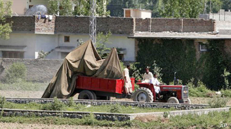 The wreckage of a US helicopter that crashed next to the wall of the bin Laden compound in Abbottabad being transported by Pakistani officials, May 2, 2011