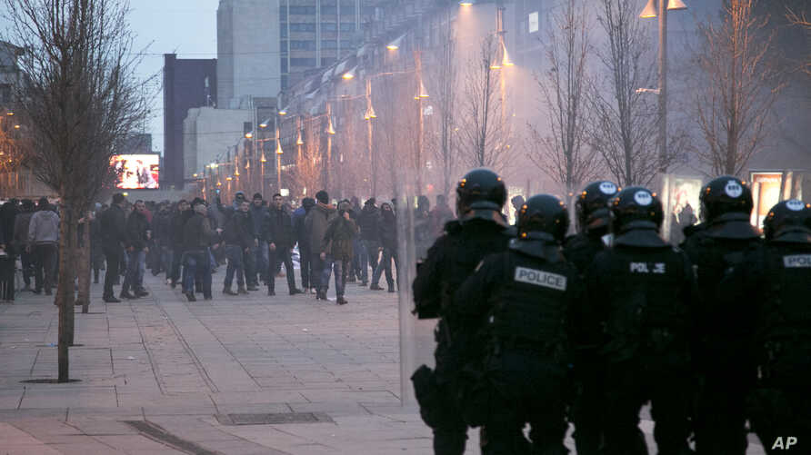 Protesters throw stones toward police in riot gear guarding the government building in Pristina, Kosovo, Jan. 24, 2015.