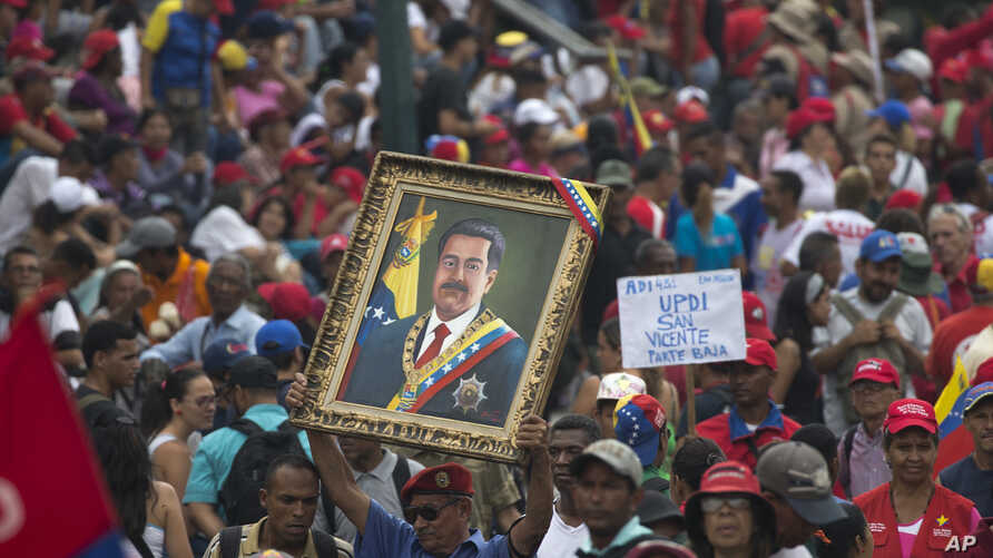 A government supporter holds up a framed image of President Nicolas Maduro during an anti-imperialist rally in Caracas, Venezuela, Saturday, March 30, 2019.