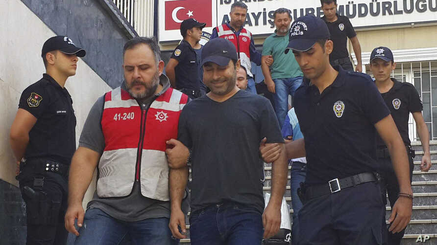 Turkish police officers escort Turkish pop singer Atilla Tas, center, to the police headquarters following his arrest, in Istanbul. Tas and 28 other people, mostly journalists, went on trial Monday, March 27, 2017, on terrorism charges for alleged li