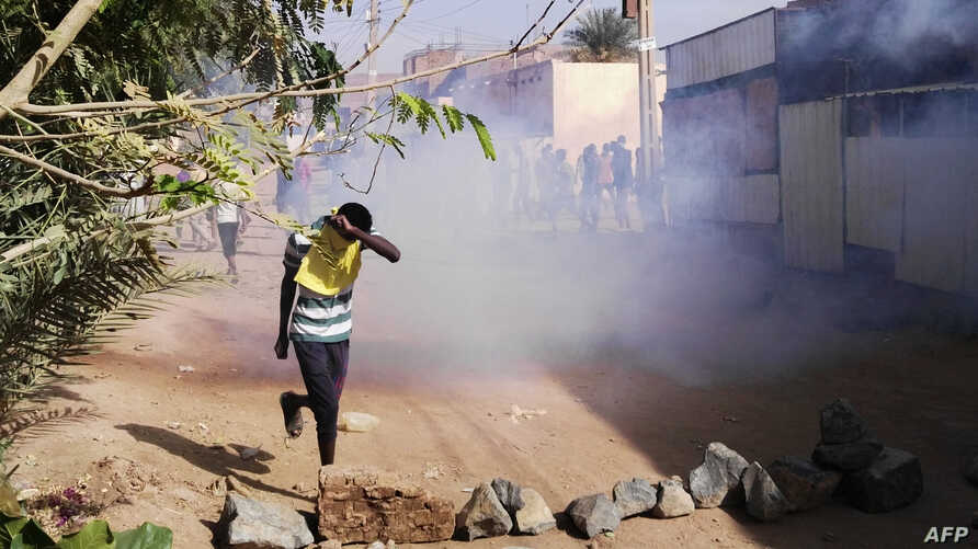 FILE - A Sudanese protester covers his face from tear gas during an anti-government demonstration in the Sudanese capital Khartoum's district of Burri, Feb. 24, 2019.