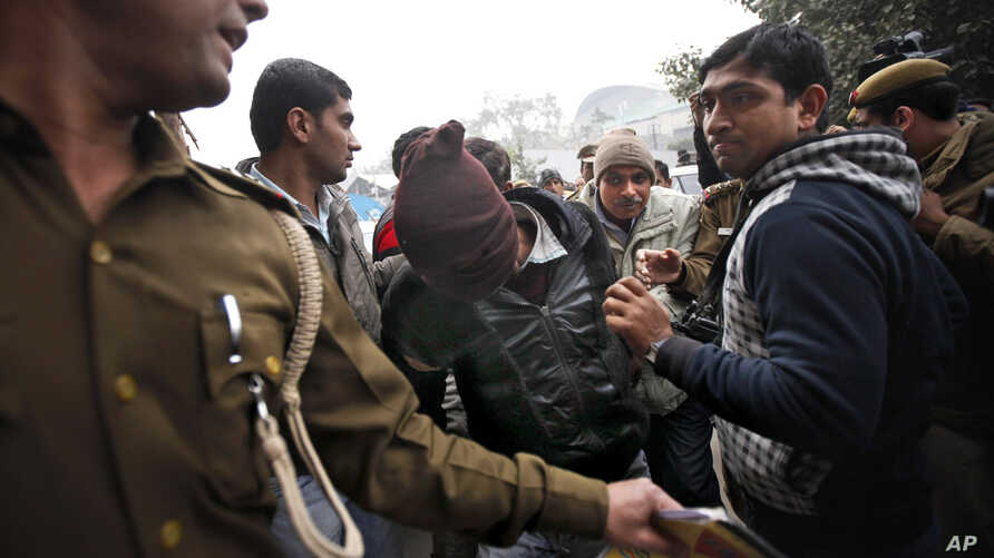 Police officials escort an accused in the gang rape of a 51-year-old Danish tourist to produce him in court in New Delhi, India,  Jan. 16, 2014.