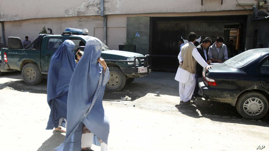 Afghan women walk past Park Palace guesthouse, May 14, 2015 after being attacked by gunmen in Kabul, Afghanistan.