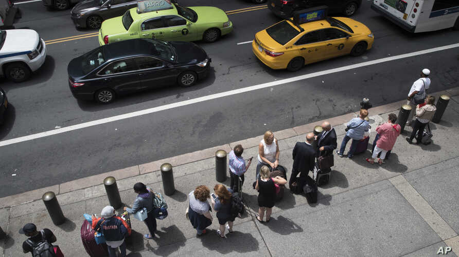 FILE - A ride-hailing car, a yellow cab and a green cab make their way across 42nd Street as passengers wait in line at a taxi stand outside Grand Central Terminal in New York, Aug. 1, 2018.