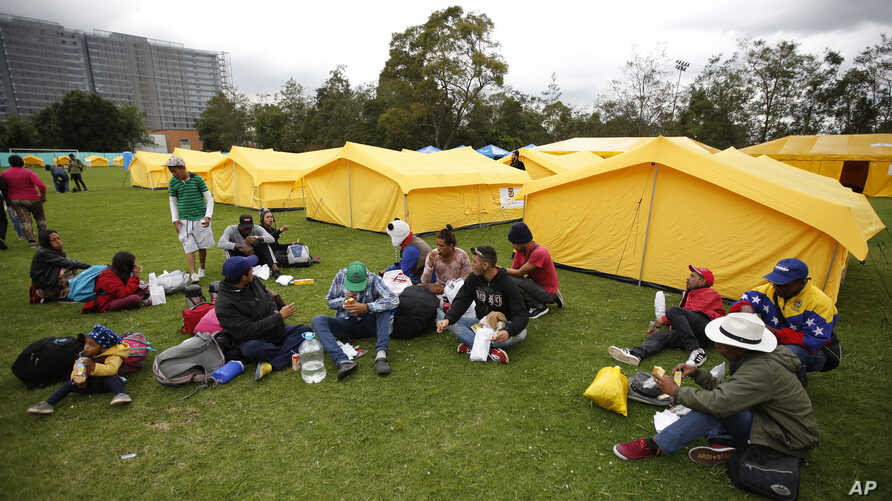 Venezuelan migrants sit upon arrival to a new, refugee-style camp set up by the government in Bogota, Colombia, Nov. 13, 2018.