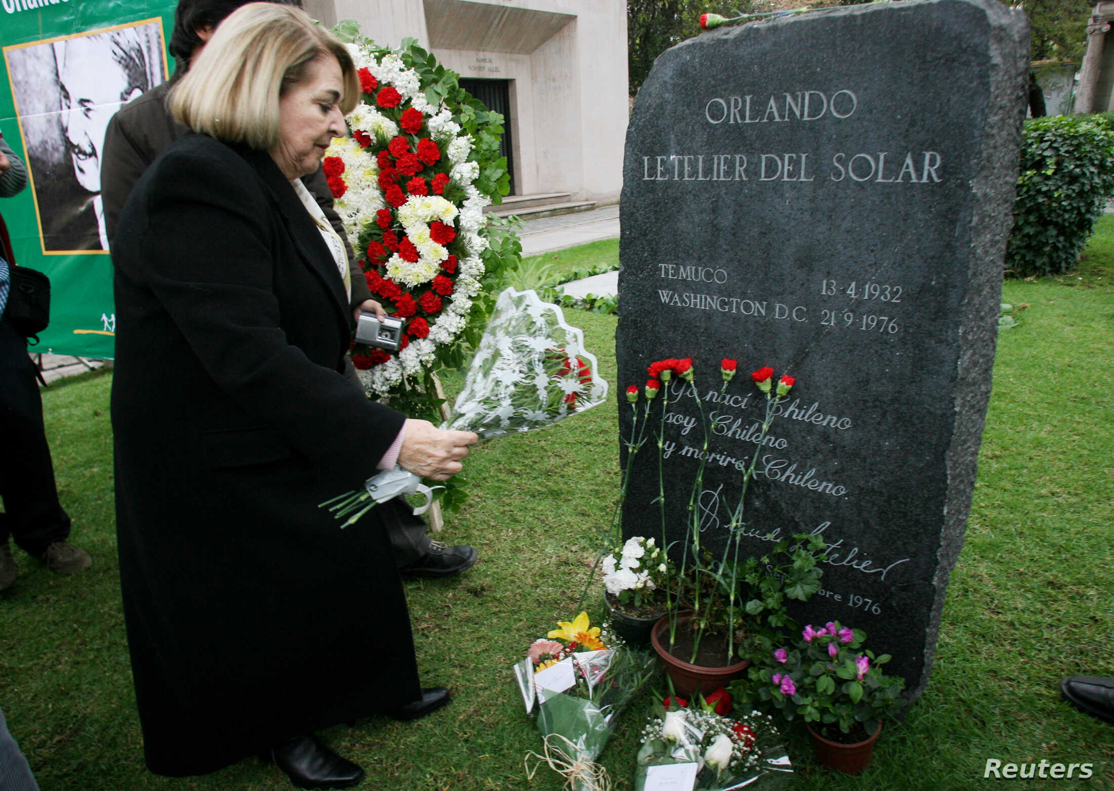 Isabel Morel, the widow of Orlando Letelier, a former Foreign Minister of Salvador Allende Government, who was killed when his car exploded 30 years ago in Washington in 1976, puts flowers on Letelier's grave in Santiago, Sept. 21, 2006.