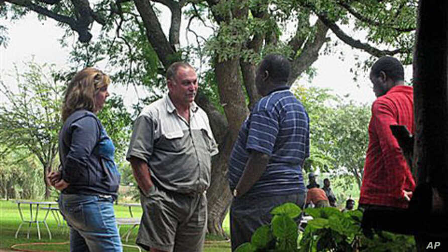 Gary Stafford and his wife talk to the Director General of National Parks, Vitalis Chadenga, after their bird sanctuary Kuimba Shiri Safari Lodge was besieged by scores of Zanu PF supporters demanding they leave, on Lake Chibero, Zimbabwe, January 22
