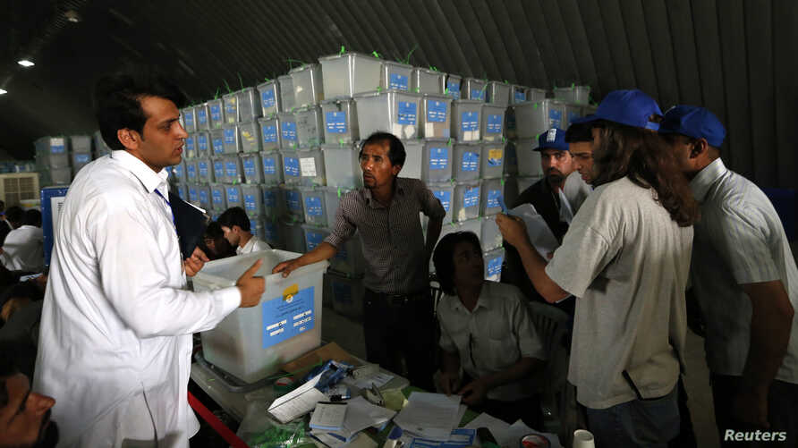 Afghan election workers count ballot papers during an audit of the presidential run-off in Kabul, Aug. 3, 2014.