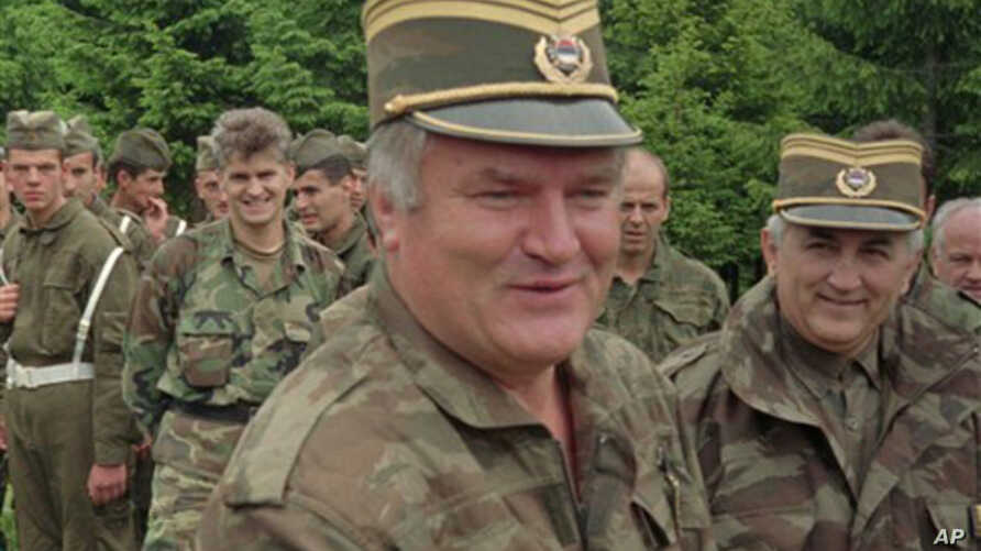 n this June 28, 1996 file photo Bosnian Serb military commander General Ratko Mladic, center, smiles as he visits troops to mark both the fourth anniversary of the founding of his Bosnian Serb army and St. Vitus' Day, the anniversary of the Serb defe