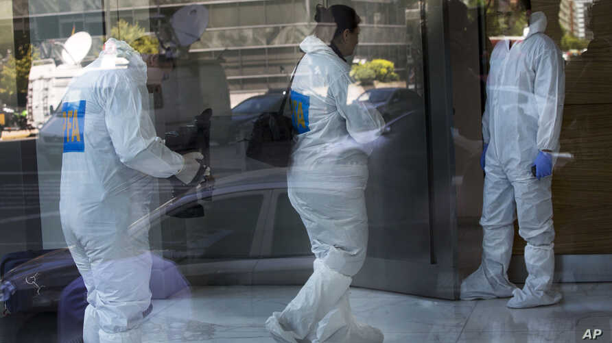 Police investigators are seen through a plate glass window as they prepare to conduct forensic analysis in the apartment where prosecutor Laberto Nisman lived and was found dead almost a month ago, in Buenos Aires, Argentina, Feb. 13, 2015.