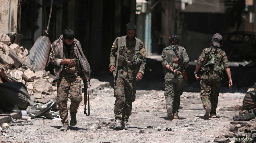 FILE - Syria Democratic Forces (SDF) fighters walk on the rubble of damaged shops and buildings in the city of Manbij, in Aleppo Governorate, Syria, Aug. 10, 2016.