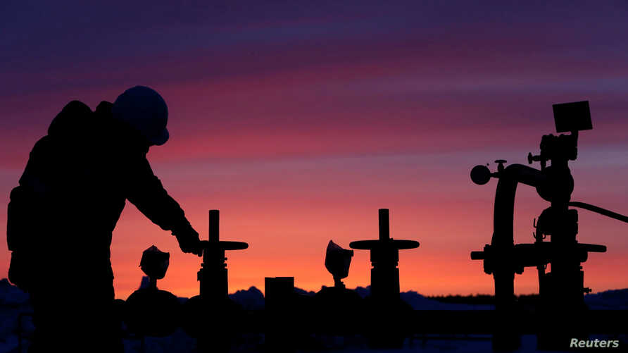 A worker checks the valve of an oil pipe at an oil field owned by Russian state-owned oil producer Bashneft near the village of Nikolo-Berezovka, northwest of Ufa, Bashkortostan, Russia, Jan. 28, 2015.