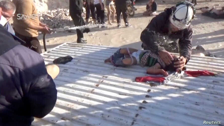 A still image taken from a video posted to a social media website on April 4, 2017, shows a civil defense member helping a child who is being sprayed with water, said to be in the town of Khan Sheikhoun, after what rescue workers described as a suspe...