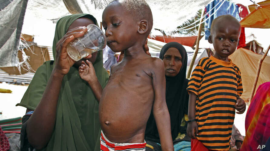 Newly displaced mother Bisharo Ali Sidow, 27, gives water to her malnourished son Hassan Hussein Ali, at a camp in the Sahal area on the outskirts of Mogadishu, Somalia, April 8, 2017.