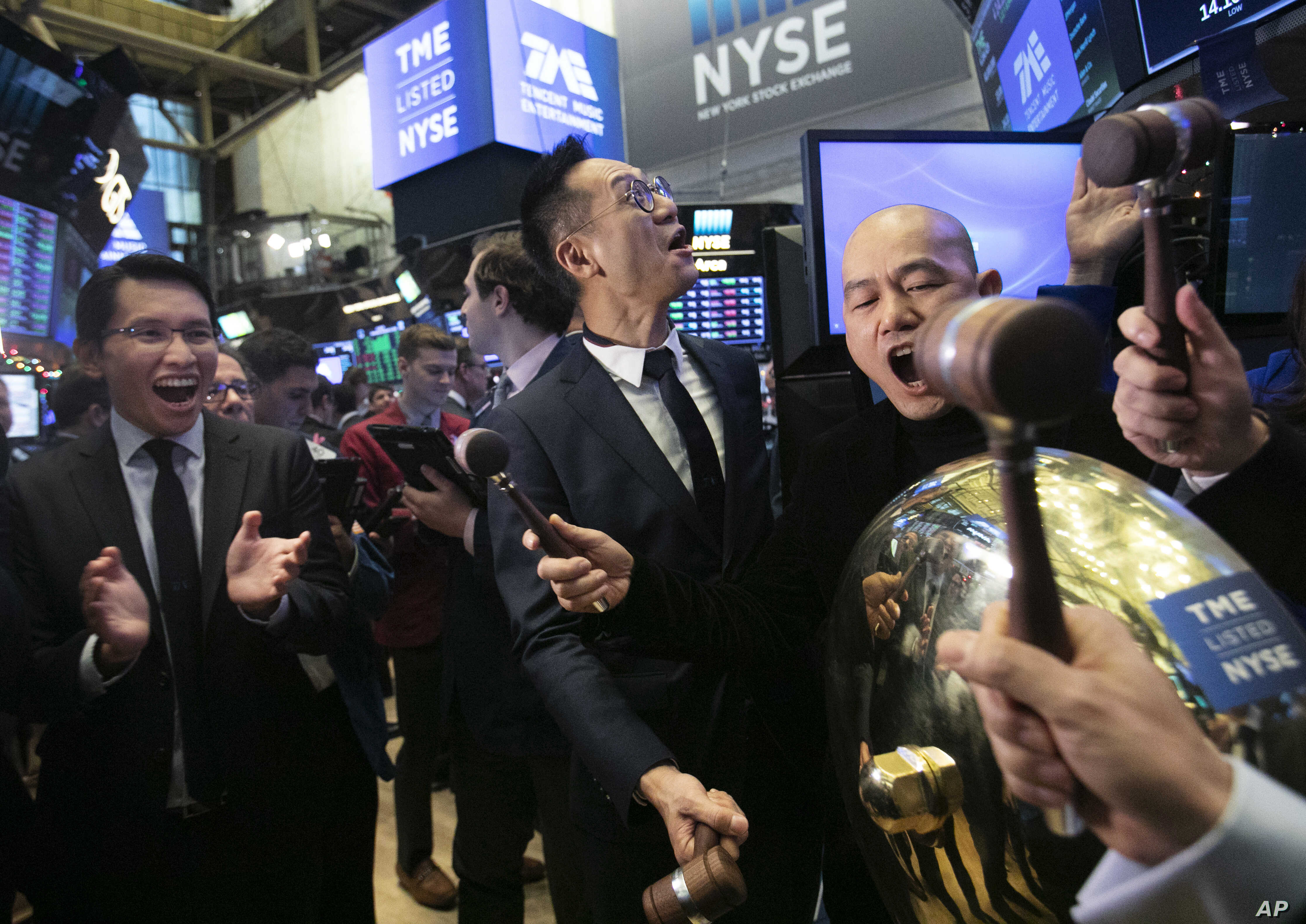 Tao Sang Tong (C), Chairman of Tencent Music Entertainment, and Co-President Guomin Xie (R) strike the bell at the New York Stock Exchange to mark the Chinese company's IPO, Dec. 12, 2018.