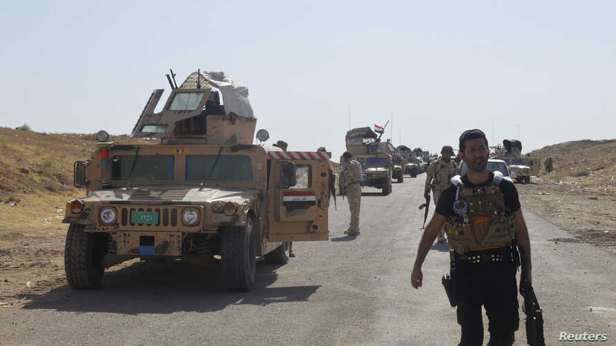 Military vehicles of Iraqi security forces are seen on a road during clashes with Islamic State (IS) militants in the Hamrin mountains in Diyala province, Sept. 20, 2014.