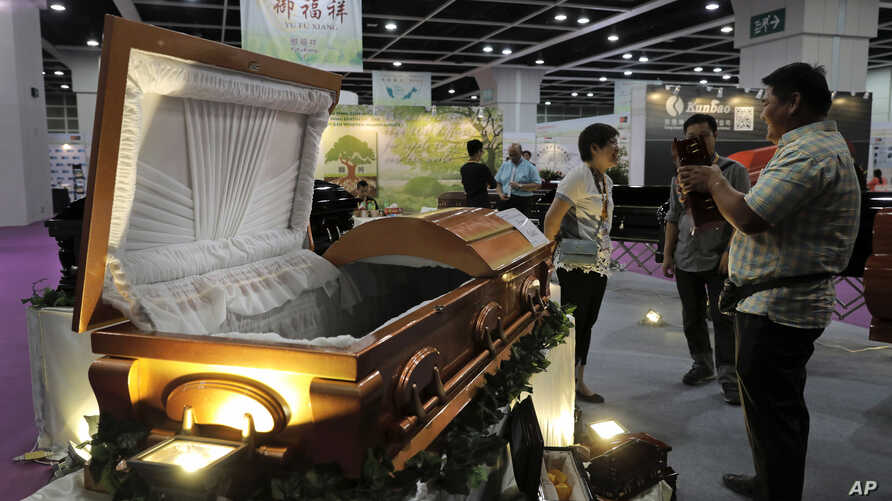 Visitors look at a paper casket at the Asia Funeral and Cemetery Expo & Conference in Hong Kong, May 18, 2017. Asia's aging population is projected to hit 923 million by midcentury, according to an Asian Development Bank, putting the region on track