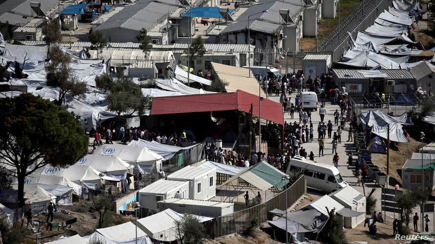 FILE - Refugees and migrants line up for food distribution at the Moria migrant camp on the island of Lesbos, Greece, Oct. 6, 2016. Two people were killed after a fire broke out at the migrant camp late Thursday, a police official said.