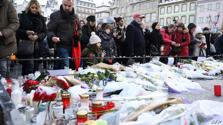 People light-up candles and deposit flowers during a gathering around a makeshift memorial at Place Kleber, in Strasbourg, on Dec. 16, 2018 to pay a tribute to the victims of Strasbourg's attack.