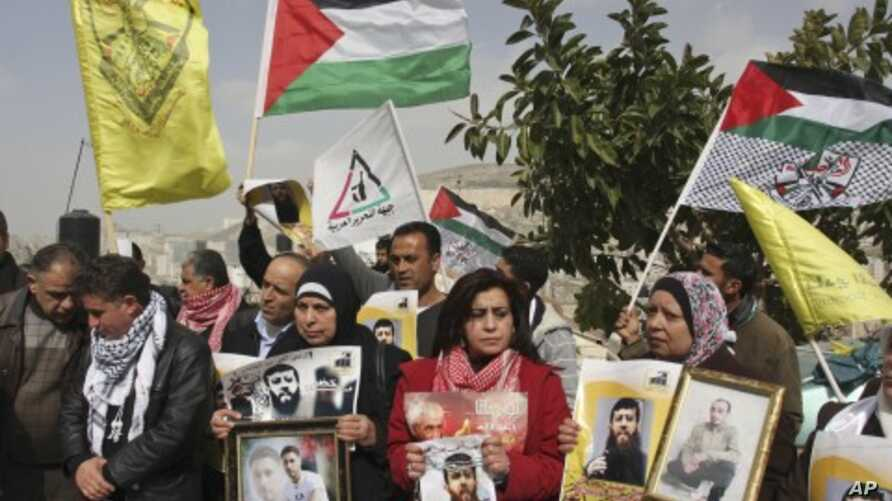 Palestinians hold flags and photographs during a protest in solidarity with Adnan, and for the release of Palestinian prisoners held in Israeli prisons, in the West Bank city of Nablus, February 8, 2012.
