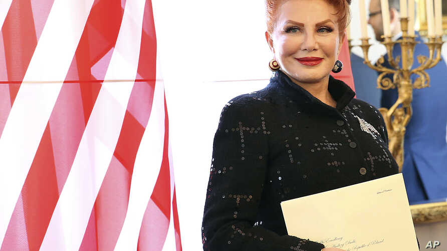 FILE - Georgette Mosbacher stands next to an American flag after receiving her credentials as new United States ambassador to Poland in Warsaw,  Sept. 6, 2018. Moshbacher has triggered anger on social media on Tuesday, Nov. 27, 2018, with a letter al