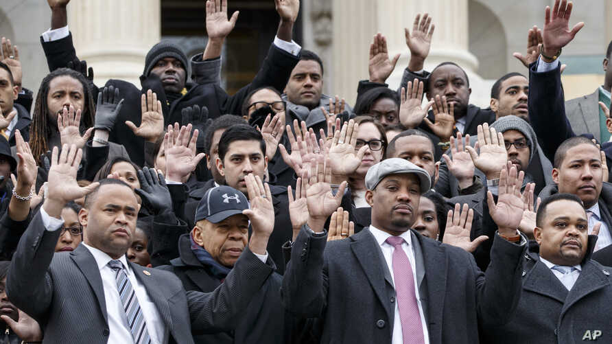 Congressional staff members gather on Capitol Hill in Washington, Thursday, Dec. 11, 2014, to raise awareness of the recent killings of black men by police officers, both of which did not result in grand jury indictments.