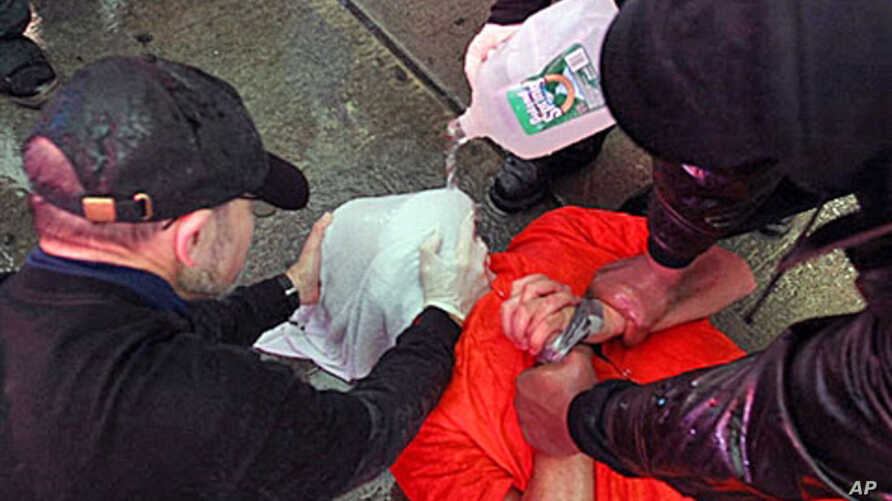 Demonstrators from the group 'World Can't Wait' hold a mock waterboarding of a prisoner (file photo)