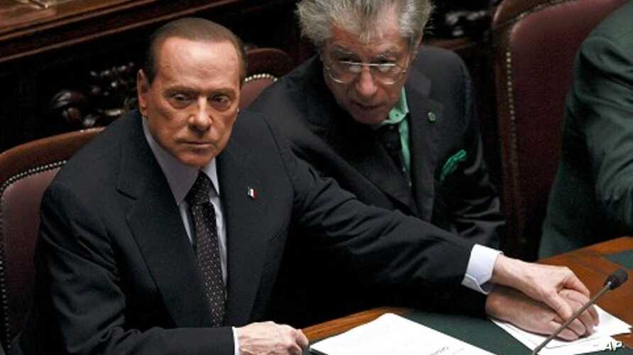 Italian Prime Minister Silvio Berlusconi, left, holds League North Party leader Umberto Bossi's hand during a finance vote at the parliament in Rome, November 8, 2011.