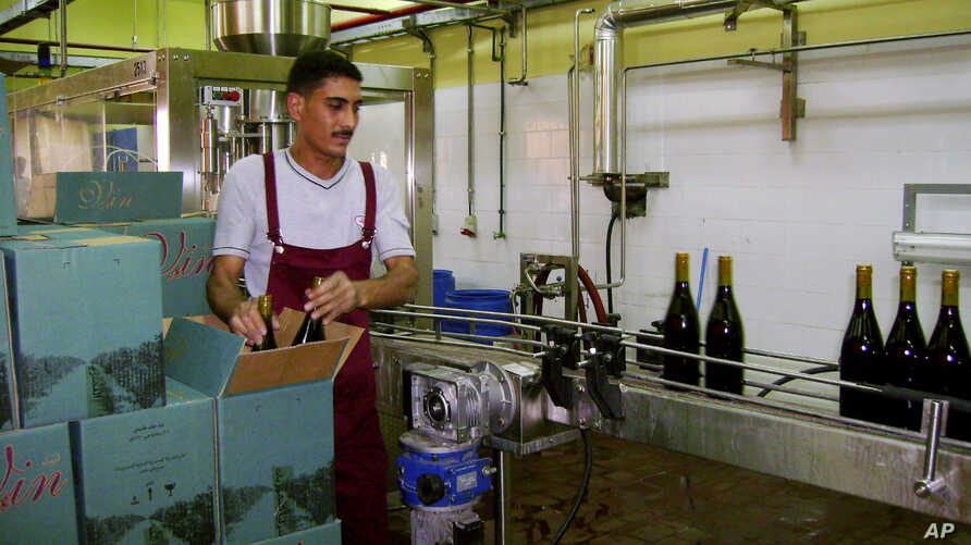 FILE - In this Sunday, May 20, 2007 file photo, a worker packs bottles of Egyptian-produced wine at the plant of EgyBev, near the Red Sea resort city of El Gouna, Egypt.