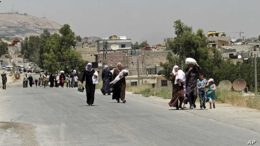 Syrians carry foodstuff as they return to the rebel-held Damascus suburb of Moadamiyeh near Damascus, July 14, 2014.