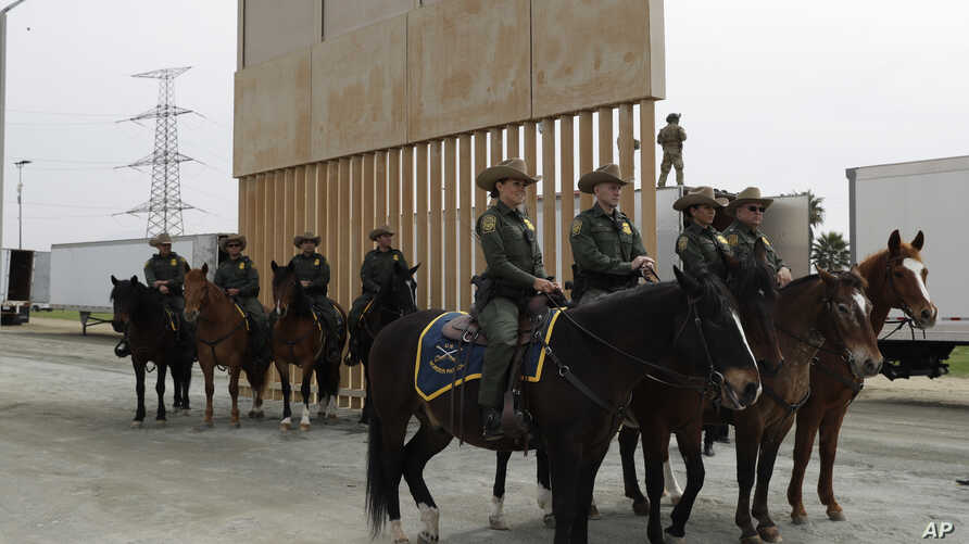 U.S. Border Patrol officers on horseback watch President Donald Trump review border wall prototypes, March 13, 2018, in San Diego.