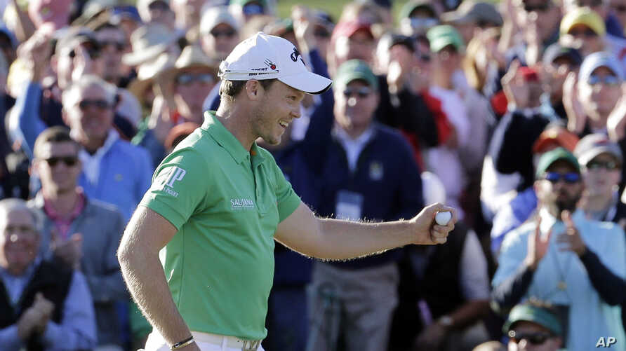 Danny Willett, of England, celebrates on the 18th hole after finishing the final round of the Masters golf tournament Sunday, April 10, 2016, in Augusta, Ga.
