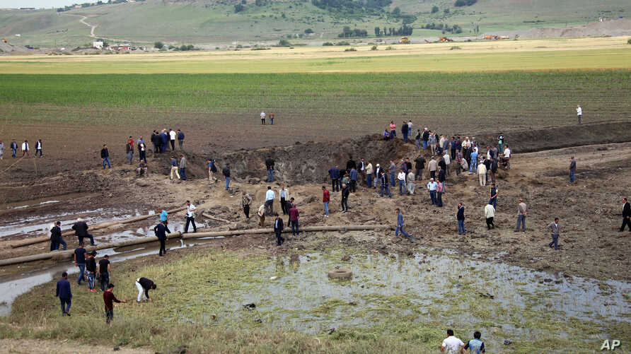 People watch the Thursday's explosion site in Sarikamis district outside Diyarbakir, Turkey, Friday, May 13, 2016.