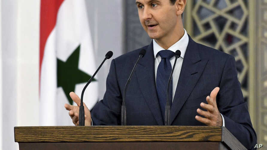 Photo released by the official Facebook page of the Syrian Presidency shows President Bashar Assad addressing Syrian diplomats, in Damascus, Aug. 20, 2017.