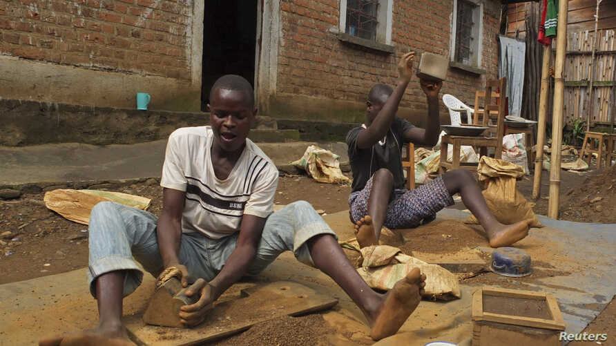 FILE - Artisanal miners crush tin ore before it is washed and then bagged ready for sale in Nyabibwe, a mining town in South Kivu, DRC.