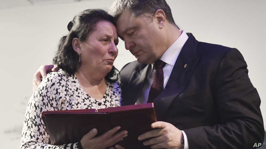Ukrainian President Petro Poroshenko, right, presents a Hero of Ukraine award to a relative of an activist killed a year ago during mass protests, at the award ceremony in Kyiv, Feb. 20, 2015.