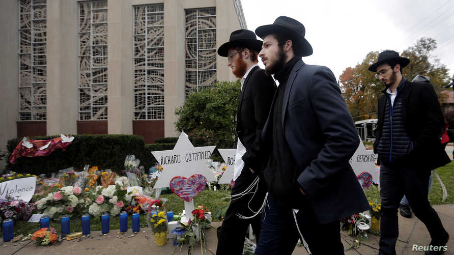 People walk past a makeshift memorial outside the Tree of Life synagogue following Saturday's shooting at the synagogue in Pittsburgh, Pennsylvania, Oct. 29, 2018.