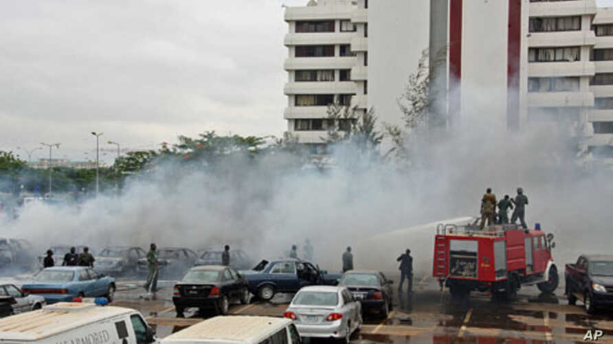 Firefighters trying to extinguish a fire after a bomb blast at the parking lot of police headquarters in Abuja, Nigeria, June 16, 2011