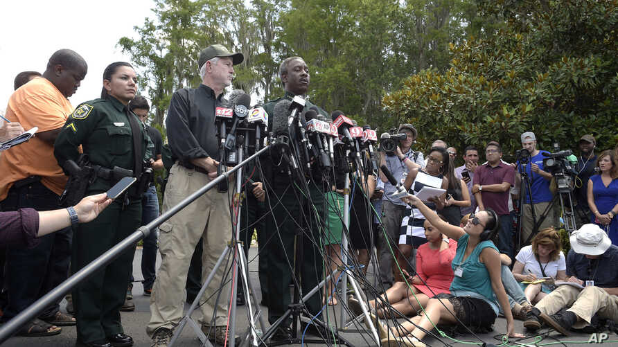 Nick Wiley, executive director of the Florida Fish & Wildlife Conservation Commission, left, and Orange County Sheriff Jerry Demings answer questions from reporters during a news conference in Lake Buena Vista, Florida, June 15, 2016, after a toddler